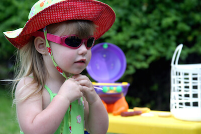 a little girl wearing a hat and sunglasses