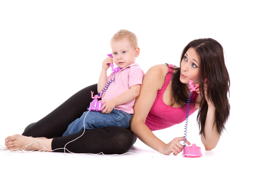 a toddler and their mom on the phone