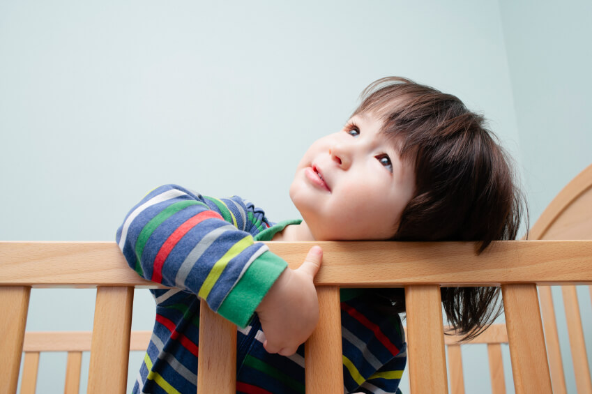 a toddler leaning out of a crib