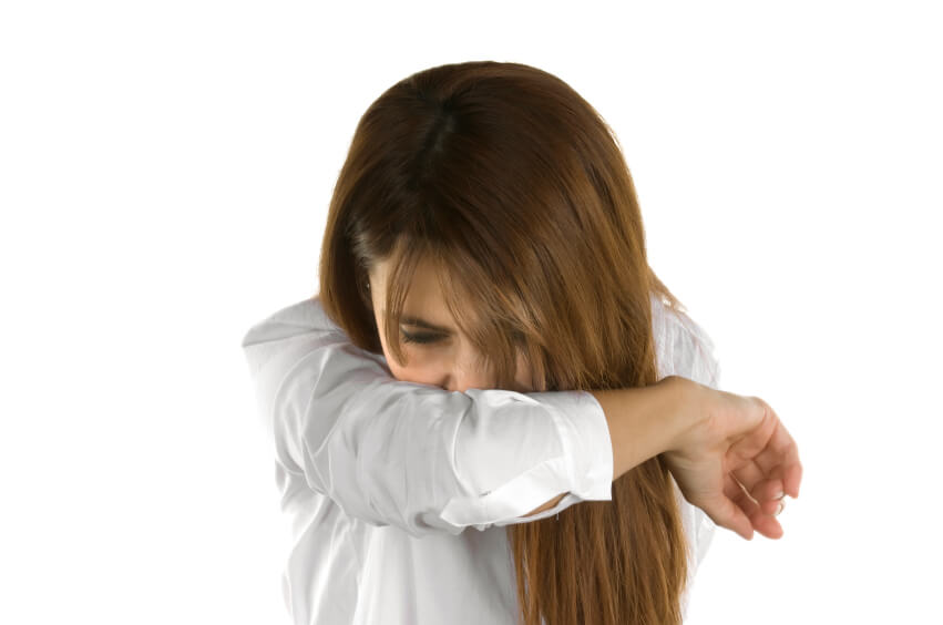 a woman wiping her nose on her shirt sleeve