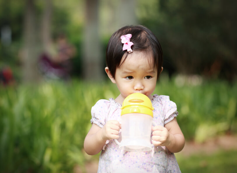 a little girl drinking from a sippy cup in a field