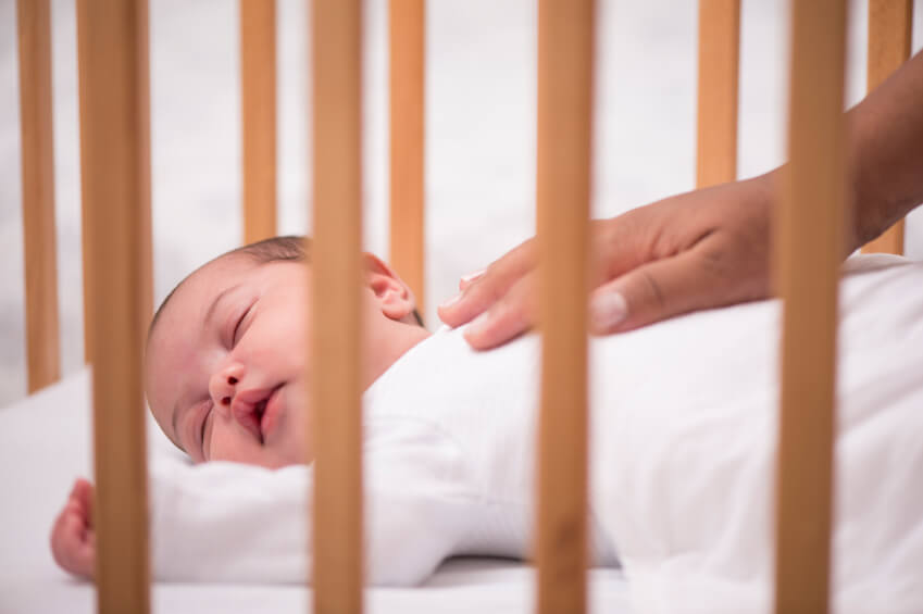a baby sleeping in a crib
