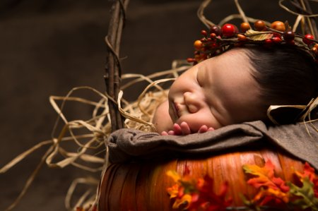 a baby sleeping next to a pumpkin