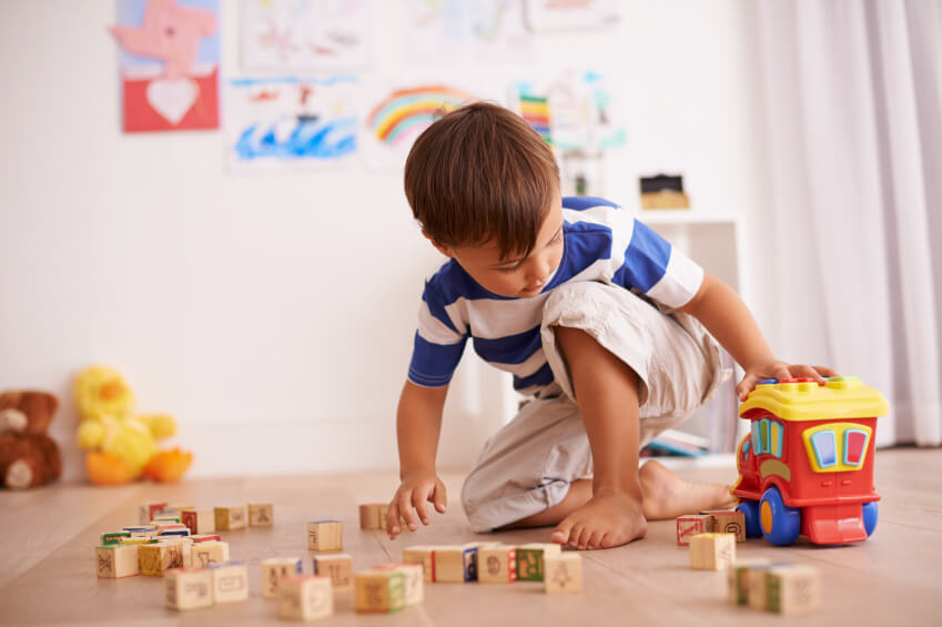 a young boy playing with toys at home