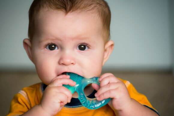 a baby chewing on a teething toy