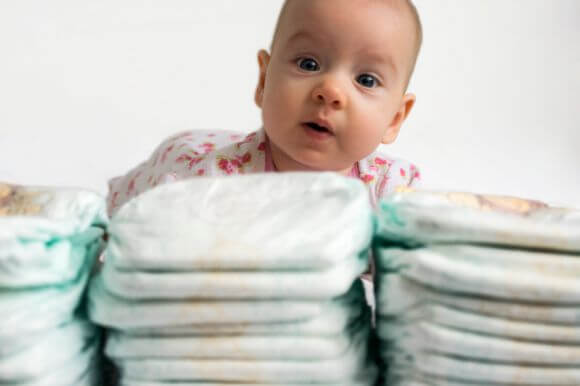 a baby sitting behind a stack of diapers