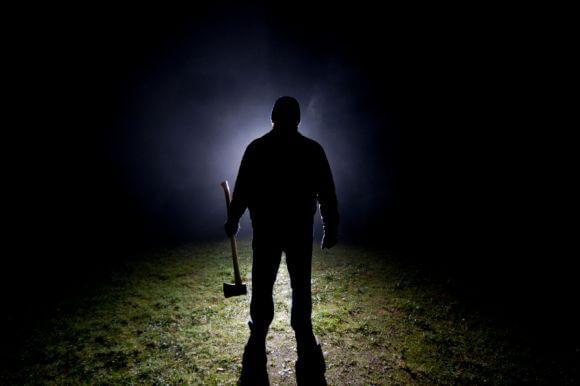 a man in the dark holding an axe