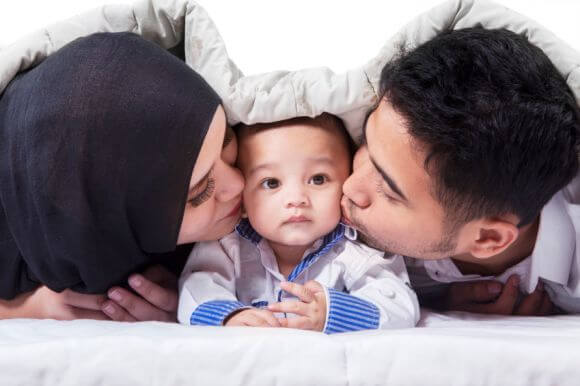 two parents kissing their baby