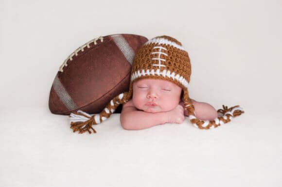 a baby dressed up as a football player