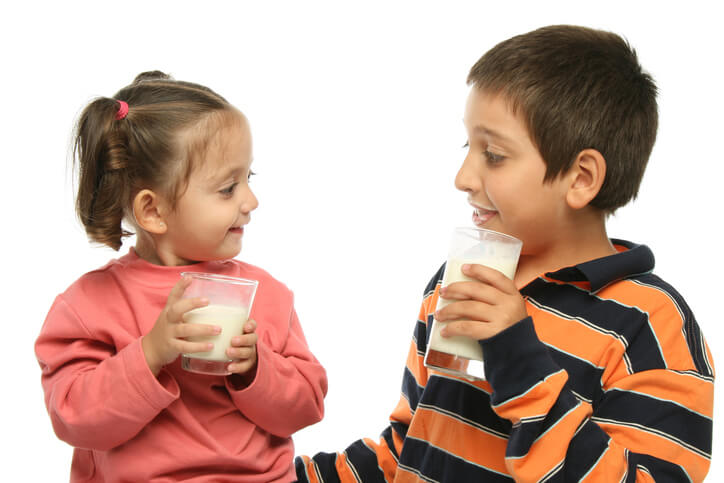 two kids drinking milk