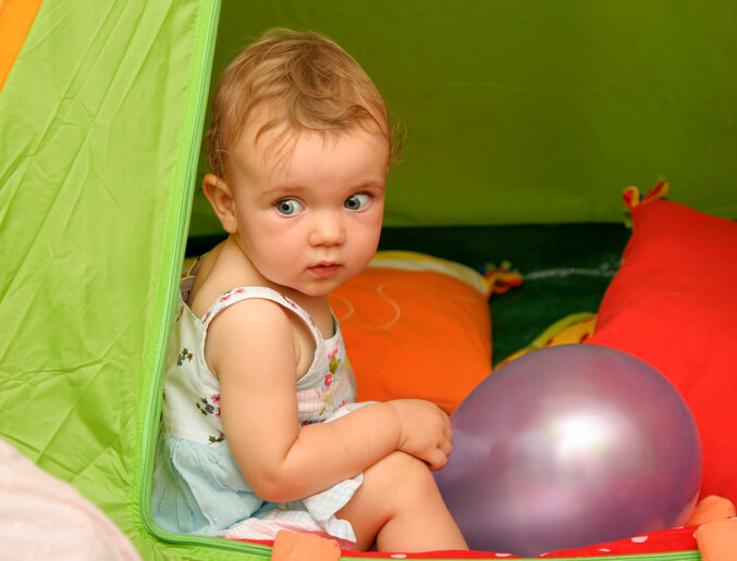 a baby sitting in a tent
