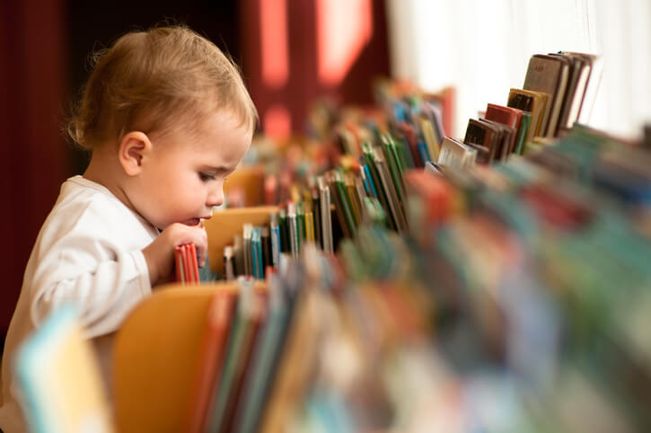 a baby looking at books in a library