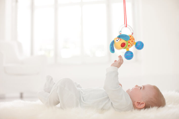 a baby lying underneath a mobile