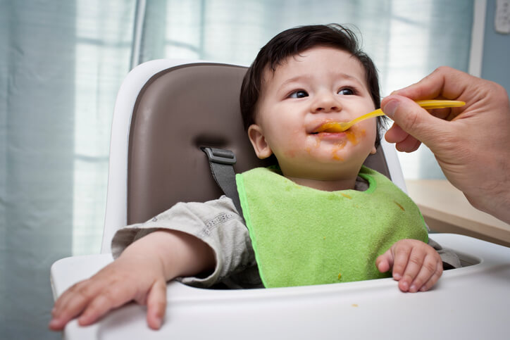 Father feeding Baby sweet potato in a high chair