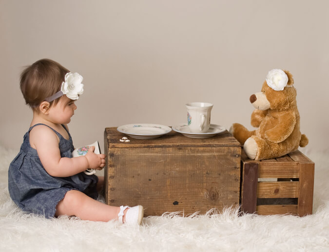 a baby having tea with her teddy