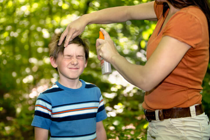 a mom spraying insect spray on her son