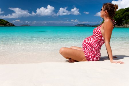 pregnant woman sitting on sand at a Caribbean beach and sunbathing