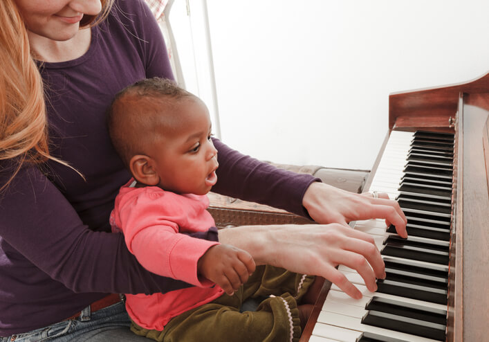 mother, adopted baby african descent multi-ethnic daughter playing piano