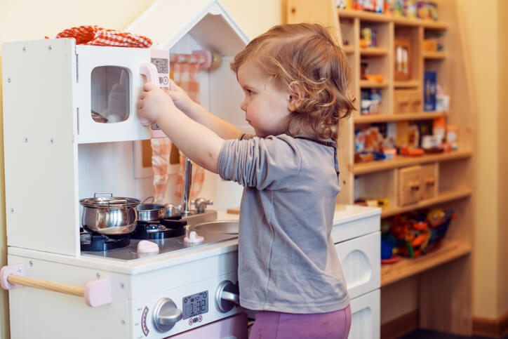 A child playing with a fake kitchen