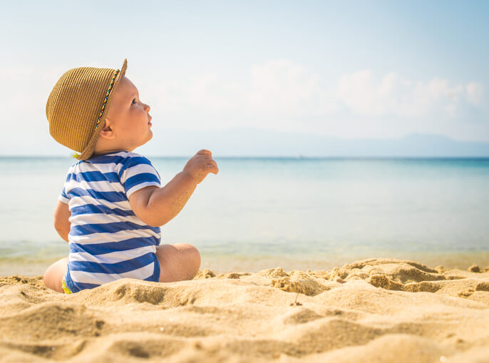 a little boy sitting on the beach