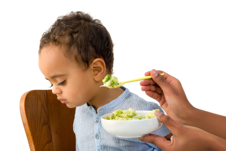 a toddler being fed vegetables