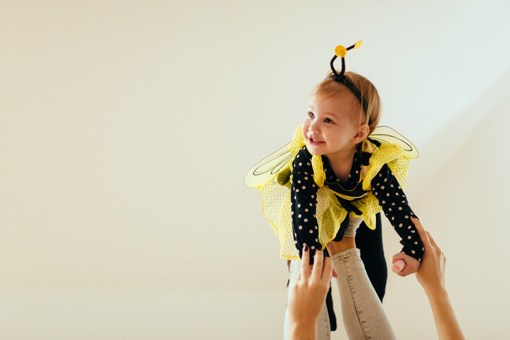 a baby girl dressed in a bee costume