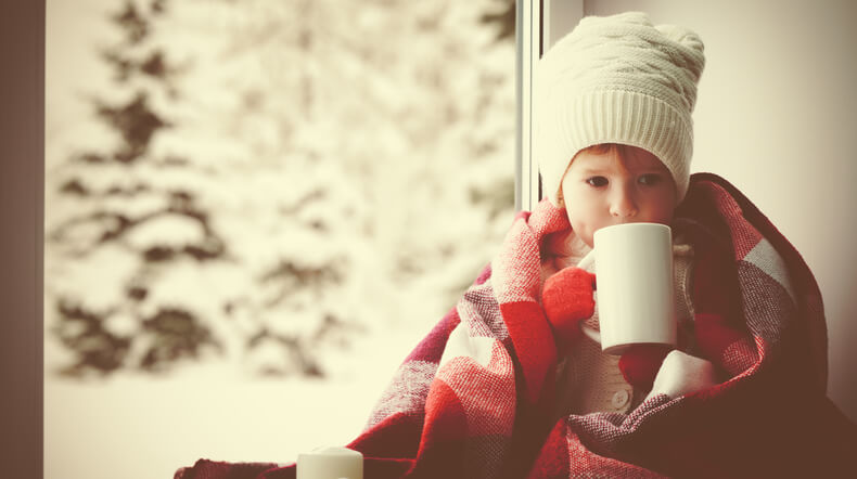 child little girl with  cup of hot tea at window