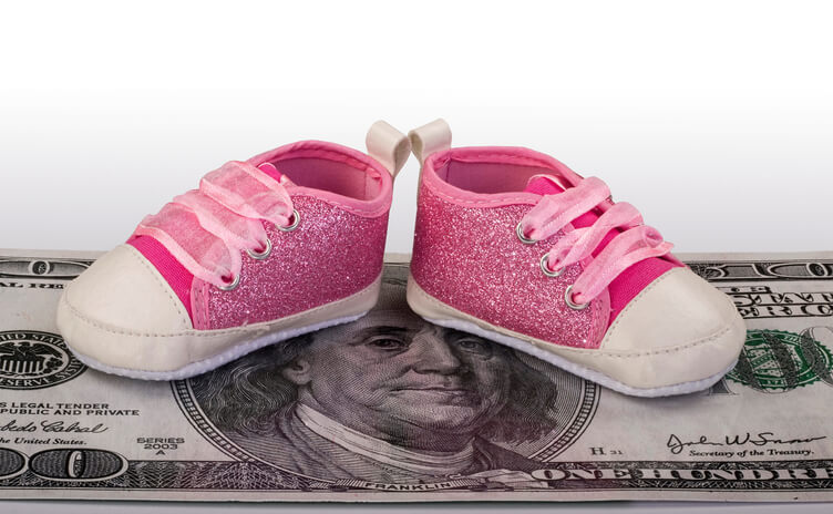 a pair of toddler shoes on some money