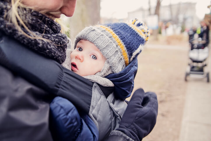 Mother with baby in carrier, outdoors in winter