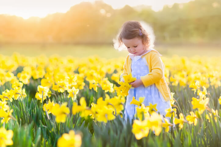 a toddler standing in a flowery field