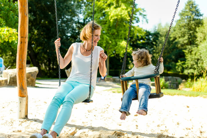 mom on the swings with her toddler