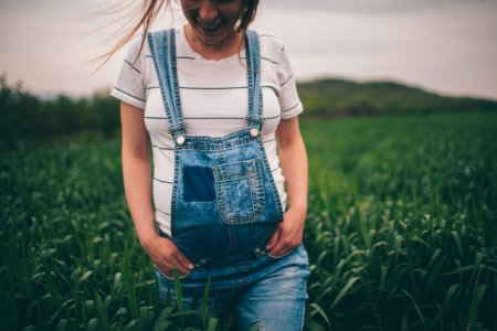 Photo of a pregnant woman walking in nature on a beautiful spring day