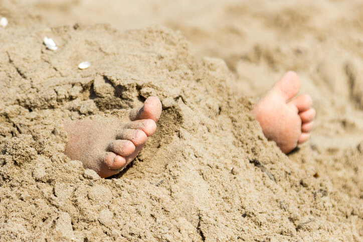 Human feet buried in sand.
