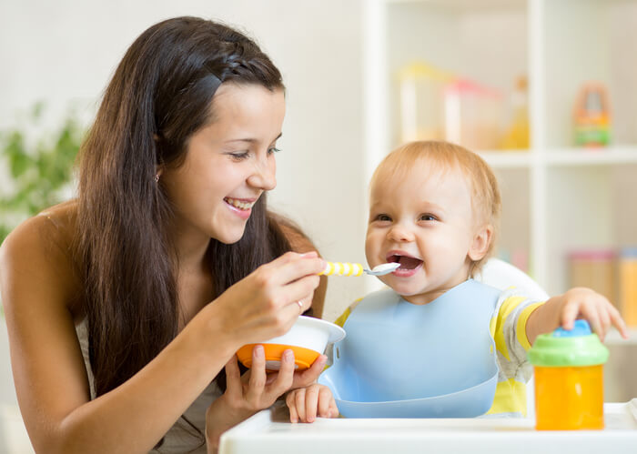 a young mom spoon feeding her baby
