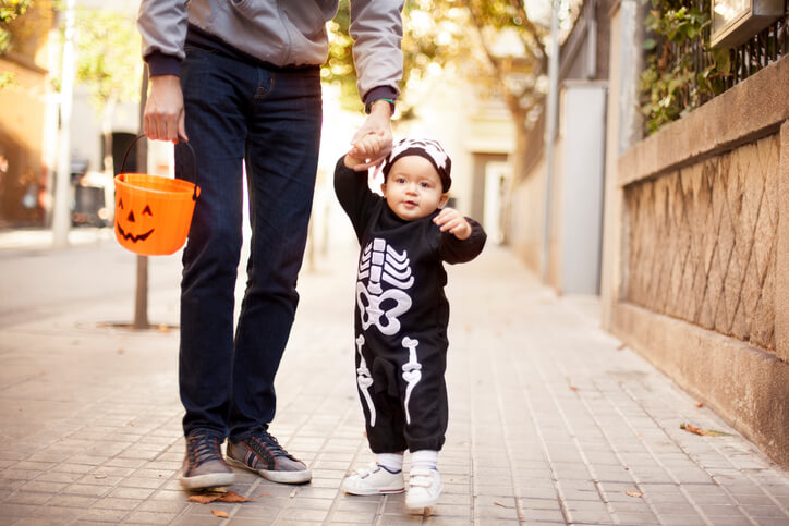 a dad taking his son trick or treating on halloween