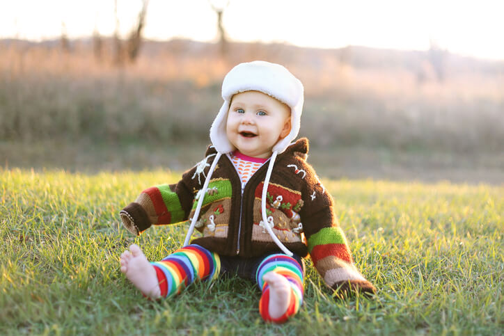 Adorable Baby Girl in Winter Hat and Sweater Laughing Outside