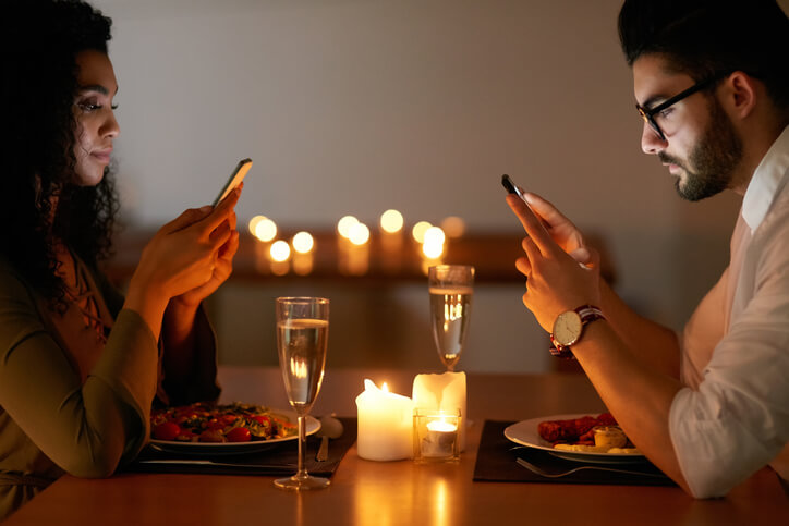 a couple both looking at their phones while on a date
