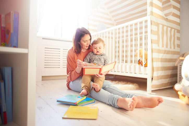 a mom reading a book to her baby