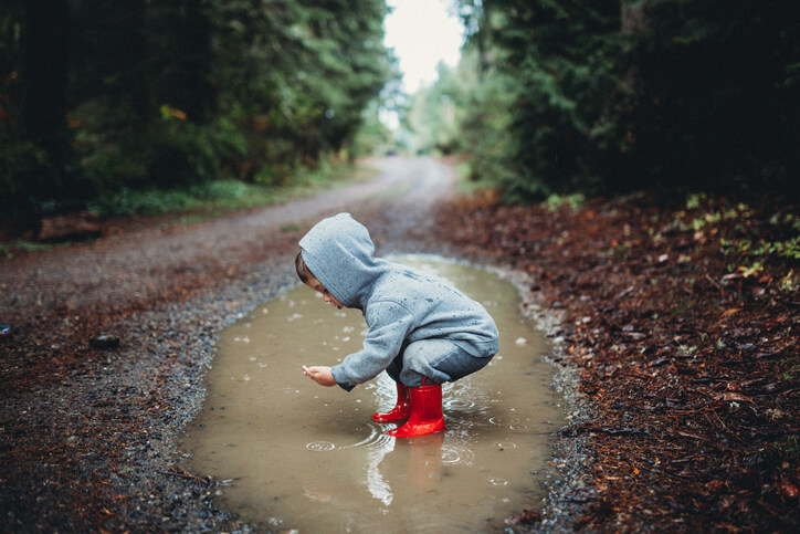 a toddler standing in a puddle of water