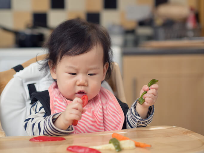 Baby girl eating roasted vegetable first time