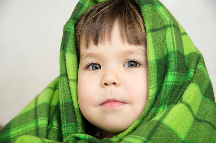 a little boy covered in a blanket