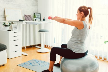 Young Pregnant Woman Exercises At Home. Exercising with dumbbells on pilates ball in her living room