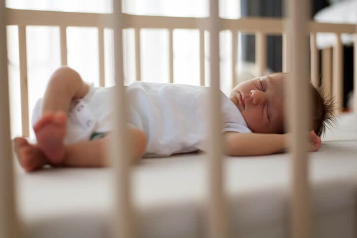 baby sleeping in a wooden crib