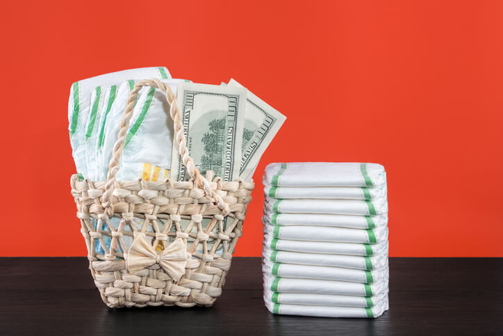 Wicker basket with baby diapers and dollars, stack of diapers