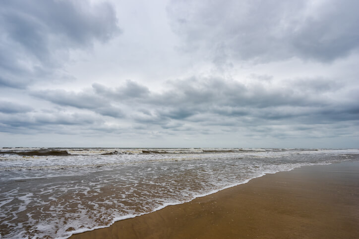 Sand beach, blue sea and white bubble wave in cloudy day