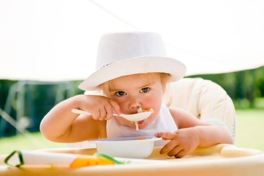 a young girl eating food from a bowl