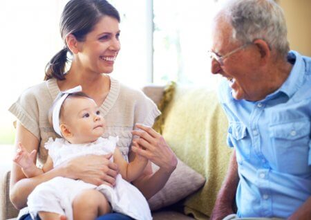 An adorable baby girl spending time with her mother and grandfather