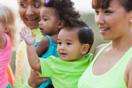Close up of two multi-ethnic mothers carrying their babies. The focus is on the mixed race (Asian and Caucasian) baby boy in the light green shirt. He is relaxed in his mother's arms.