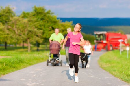 Family with three children, one baby lying in a baby buggy, walking down a path outdoors, two kids are running ahead, there is also a dog
