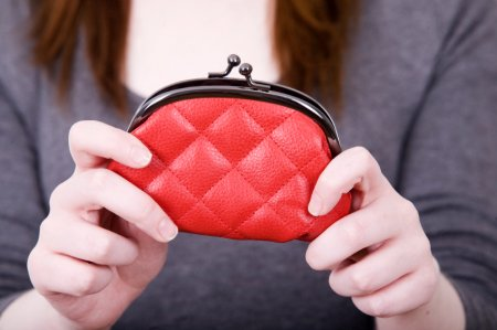 a woman holding up a red purse